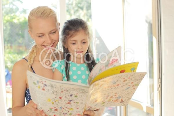 女の子と絵本を読むワンピースの女性5の写真