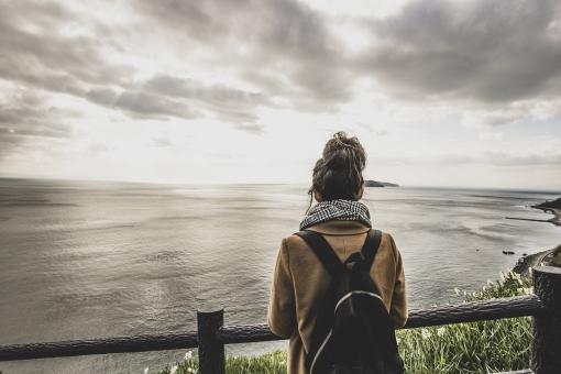 海を眺める女性の後ろ姿の写真