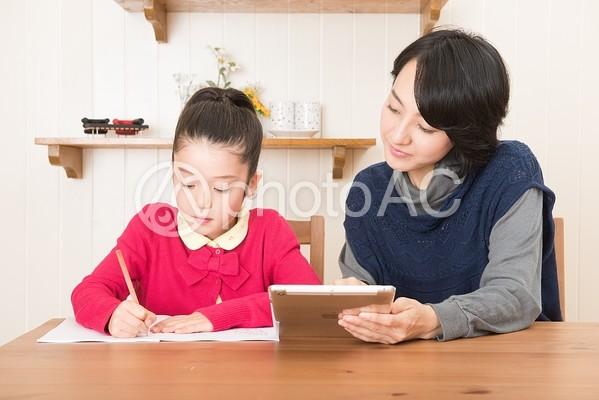 娘の勉強を見るお母さん13の写真