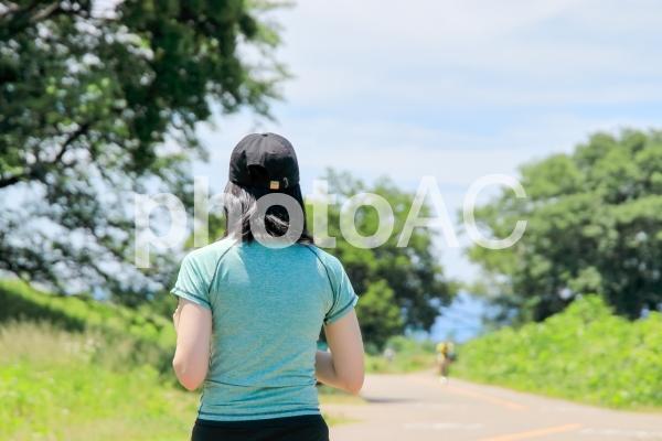 ランニングキャップを被って走る女性の写真