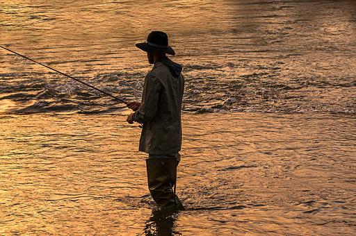 川釣り 夕方 夕日 黄昏 逆光 シルエット 川 河 川の中 河の中 ハット 帽子 立つ 水面 釣り フィッシング フライフィッシング アウトドア 魚 釣り人 フィッシャーマン 人物 男性 外国人 白人  ポートレート 景色 風景 自然 趣味 ホビー 後ろ姿 釣り竿 ロッド リール 投げ釣り キャスティング