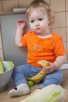 赤ちゃん 外国人 子供 子ども こども 女の子 女児 乳児 ライフスタイル 部屋 室内 屋内 金髪 カワイイ 可愛い かわいい 半袖 夏服 春服 SS オレンジ キッチン 台所 座る まな板 料理 調理 野菜 フルーツ カット 切る 食べる 齧る かじる バナナ りんご リンゴ 白菜 mdfk037