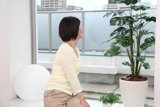マダム おばさん 熟年 中年 老人 人物 女 おばあちゃん 後ろ姿 日本人 60代 腰掛ける 座る 窓辺 窓際 眺める 風景 景色 マンション ベランダ くつろぐ 寛ぐ 植木 植木鉢 植物 緑 グリーン 部屋 屋内 室内 暮らし 生活 ライフスタイル シニアライフ mdfs002