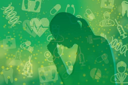 健康にストレスを抱える女性-緑背景の写真