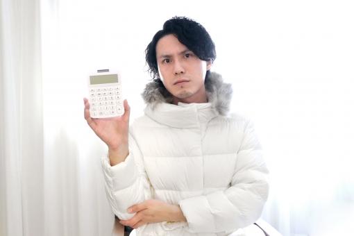 電卓と険しい表情の男性の写真