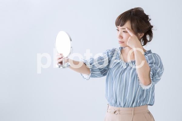 鏡で眉毛を見る女性の写真
