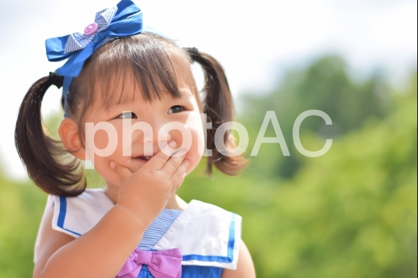 口をおさえて笑う子供の写真