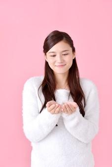 人物 女性 日本人 若者 若い  20代 美人 かわいい ロングヘア カジュアル  ラフ 私服 セーター ニット 屋内  スタジオ撮影 背景 ピンク ピンクバック ポーズ  おすすめ 両手 手のひら 掌 見る 正面 上半身 笑顔 微笑む mdjf007