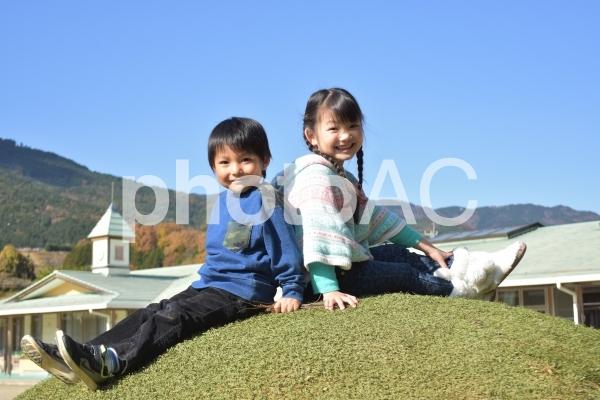 お山の上で座る子供たちの写真