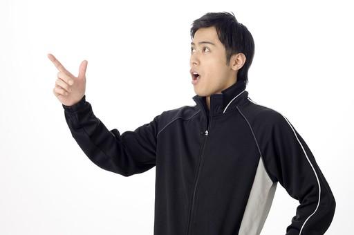 人物 人 男性 男 大人 日本人 20代 スタジオ撮影 白背景 白バック スポーツウェア ジャンバー ウィンドブレーカー 手 指 サイン ポーズ 人差し指  チョキ あ! あそこだ あれだ 発見 見つけた 横向き その通り 正解 若い スポーツ 運動 ジム インストラクター コーチ トレーナー 指さす 指差し 驚き 驚く mdjm025