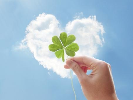 四つ葉のクローバーを持つ手とハート型の雲と青空の写真