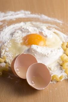 たまご 卵 玉子 エッグ 卵色 料理 食べ物 食材 食料 物撮り 屋内 人物なし 上から 1個 レシピ 鶏 にわとり ニワトリ 粉 白 木 ベージュ 殻 混ぜる パスタ 板 小麦粉