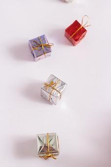 箱 小箱 プレゼント 贈り物 手土産 土産 ゴールド  金色 シルバー レッド 赤 ブルー 青 銀色 光沢 ギフト 贈答品 印象的 おくり物 5個 ボックス 屋内 人物なし 物撮り 包装紙 紙 置く 集める 上から視線 反射 高級感 乱雑 転がる