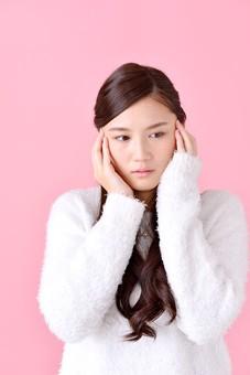 人物 女性 日本人 若者 若い  20代 美人 かわいい ロングヘア カジュアル  ラフ 私服 セーター ニット 屋内  スタジオ撮影 背景 ピンク ピンクバック ポーズ  おすすめ 上半身 悩む 考える 困る 困惑 迷う  憂鬱 mdjf007