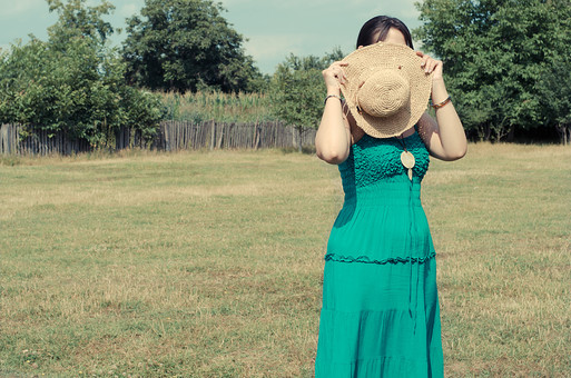 外国 海外 屋外 野外 自然 人物 1人 外国人 白人 セルビア人 大人 若い 女性 女 女の子 膝から上 ブルネット 黒髪 セミロング まとめ髪 ひっつめ髪 無造作ヘア 普段着 青緑の服 ワンピース ノースリーブ キャミソールワンピース ネックレス ペンダント レザーコード ブレスレット アクセサリー 帽子 麦わら帽子 植え込み 低木 木 木立 芝生 柵 隠す 隠れる 恥ずかしい まぶしい 空 mdff021