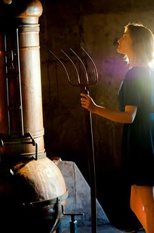 外国人 女性 一人 色白 美しい 美脚 青 紺 ワンピース 半袖 ミニスカート 金髪 ピッチフォーク 干し草用フォーク 農用フォーク フォーク 1本 左手 逆さ 逆 立てる 横顔 横向き 上向き 昼 屋内 朝日 夕日 日差し 田舎 農家 ストーブ 焼却炉 暖炉 煙突 mdff017