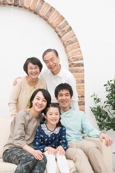 人物 日本人 家族 親子 ファミリー  三世代 二世帯 5人 両親 義両親  こども 子供 孫 娘 女の子  小学生 笑顔 スマイル 仲良し 屋内 部屋 室内 リビング ソファ 座る 集まる 団欒 だんらん 寄り添う  mdjf017 mdfk014 mdfs003 mdjm016 mdjms004