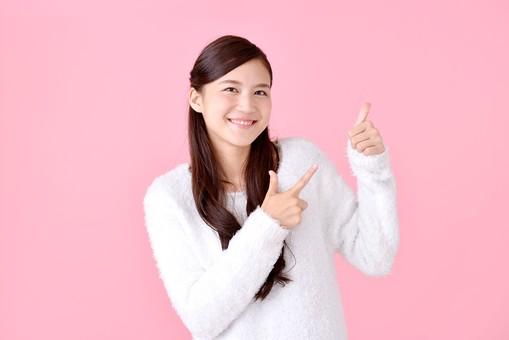 人物 女性 日本人 若者 若い  20代 美人 かわいい ロングヘア カジュアル  ラフ 私服 セーター ニット 屋内  スタジオ撮影 背景 ピンク ピンクバック ポーズ  おすすめ 指差し 指さす 上 注目 説明 案内 アドバイス 笑顔  グーサイン 良い 大丈夫 サムズアップ mdjf007