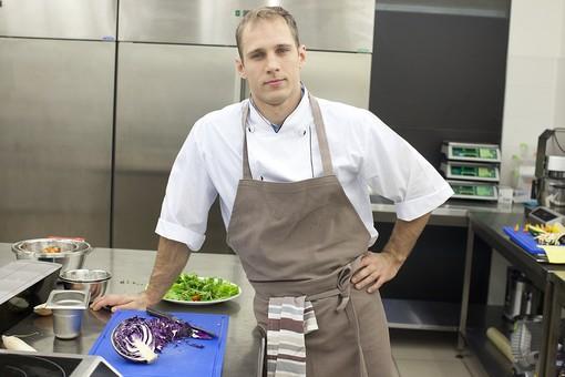 外国人 厨房 台所 キッチン 料理 調理  コック シェフ 料理人 まな板 レストラン 仕込み 下準備 野菜  エプロン 料理長 ふきん カメラ目線 男性 腰に手 レッドキャベツ 紫キャベツ 冷蔵庫 青 銀 シルバー  mdfm030