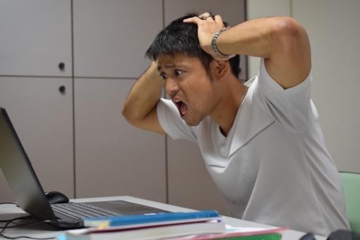 パソコンを見て頭を抱える男性の写真
