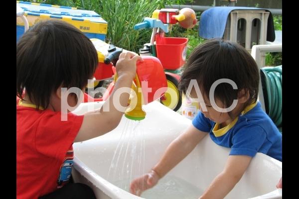 水遊びをする双子の写真