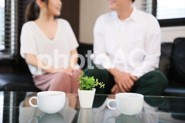 コーヒーを飲みながら会話する男女 の写真