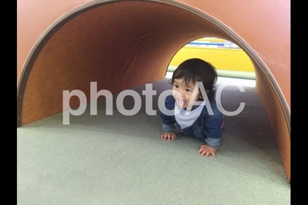 トンネルでハイハイをする赤ちゃんの写真