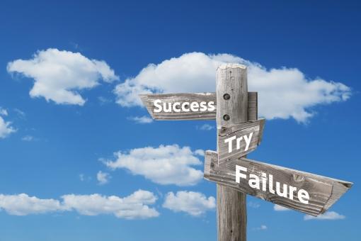 ビジネスの成功・失敗・挑戦の木製道しるべと青空の写真