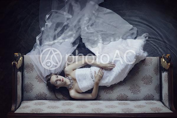 ドレスでソファに寝る女性の写真