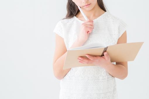 ノートを見て考える女の子の写真