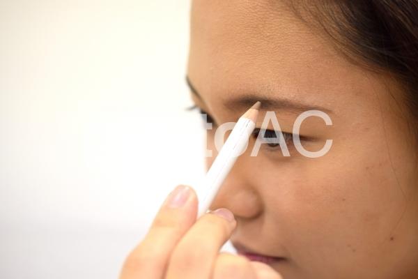 アイブロウペンシルで眉を描く女性の写真