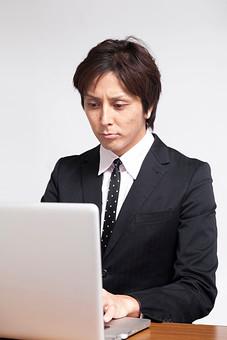 人物 日本人 男性 若い 若者  20代 サラリーマン ビジネスマン 屋内 白バック  白背景 会社 オフィス 書類 報告書 レポート 作成 パソコン PC デスクワーク 真面目 スーツ 仕事 ビジネス 机 オーバーリアクション mdjm009
