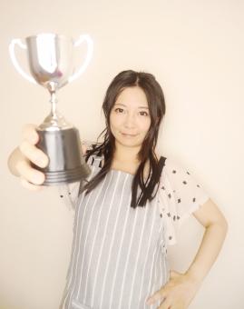 優勝トロフィーを持ったエプロン姿の女性の写真