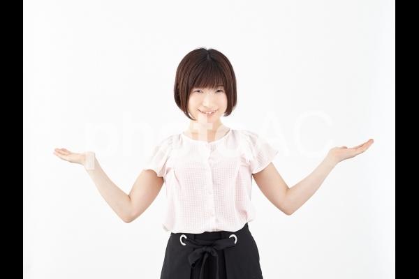 両手を上げ比較する女性(笑顔)の写真