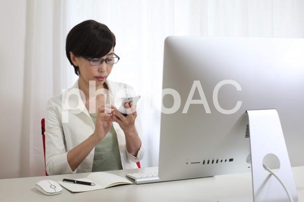 パソコンの前でスマホを見る女性の写真