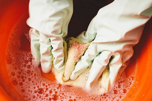 クリーナー 汚れ 木目 床 テーブル 机 屋内 掃除 洗剤 家庭 清潔 綺麗 きれい 家事 濯ぐ 衛生 労働 クローズアップ  黄緑 タオル 布 雑巾 ゴム手袋 両手 汚れ 赤 インク 絵具 水 洗面器 タライ 朱 オレンジ 橙 漬ける 押す 洗う 泡