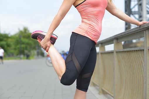 外国人 女性 女 20代 30代 若い 下半身 運動 スポーツ ジョギング 体操 ストレッチ 準備運動 ウォーミングアップ 足を持つ 片足立ち 体をひねる ランニングウェア スポーツウェア ランニングシューズ 背景 遊歩道 リバーサイド 公園 パーク