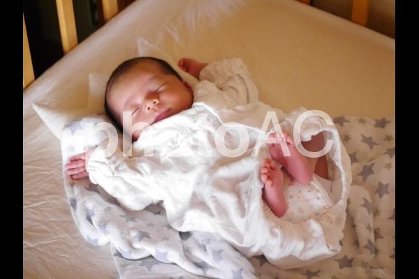 ベビーベッドで眠る赤ちゃん(新生児)の写真
