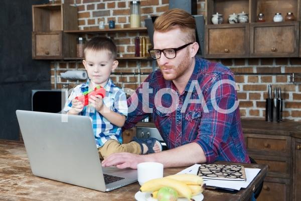 自宅で息子の世話をしながら仕事するお父さんの写真