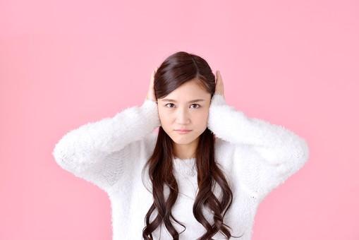 人物 女性 日本人 若者 若い  20代 美人 かわいい ロングヘア カジュアル  ラフ 私服 セーター ニット 屋内  スタジオ撮影 背景 ピンク ピンクバック ポーズ  おすすめ 上半身 耳を塞ぐ うるさい 騒音 雑音 シャットアウト mdjf007