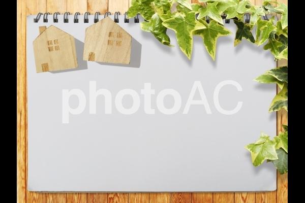 スケッチブックと家の積木と植物背景素材の写真