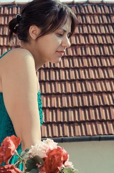 外国 海外 屋内 屋外 人物 1人 外国人 白人 セルビア人 大人 若い 女性 女 女の子 上半身 横向き 横顔 ブルネット 黒髪 セミロング まとめ髪 ひっつめ髪 無造作ヘア 空 陽射 植物 造花 薔薇 バラ ばら 赤 ピンク 花 葉 香る ベランダ バルコニー 屋根 屋根材 微笑み 微笑 笑顔 アップ mdff021