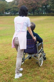 老人 高齢者 お年寄り シニア 男性 男 おとこ  2人 二人  介護士 看護師 エプロン  介護 不自由 椅子 ヘルパー 屋外 緑 木々 木 ジャケット ズボン 青  車いす 車椅子    座る  握る 手 押す 歩く 女性 おんな 女 芝生 全身 後ろ姿 散歩 外出 mdjf017 mdjms004