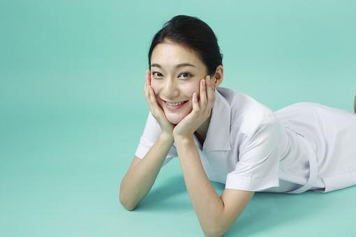 人物 女性 日本人 20代 30代  仕事 職業 医療 病院 看護師  ナース 医者 医師 女医 白衣  看護 屋内 スタジオ撮影  背景 グリーンバック  おすすめ ポーズ 上半身 寝転ぶ 寝そべる 頬杖 両手 笑顔 薬剤師 mdjf010 グリーン 緑