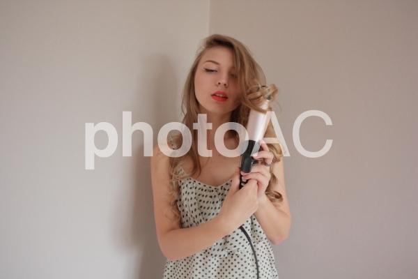 カール用ヘアアイロンを持つ外国人女性5の写真