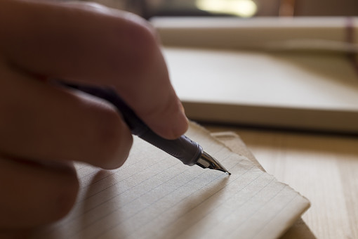 学生 記者 ライター ペン 万年筆 ペン先 ペンポイント グリップ 紙切れ 罫線 スケッチ レポート 筆記 メモ 書く 描く 記す まとめる 持つ 握る 執筆 右手 右利き 書斎 部屋 机 テーブル デスク 接写 室内 屋内 日光