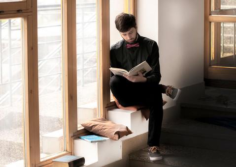 本 ブック 書物 書籍 図書 読書 読む 趣味 勉強 人物 男性 男 外国人 若い 若者 髭 20代 全身 ページ 捲る めくる 開く 座る クッション 窓際 窓辺 段々 段差 階段 俯く 脚を組む 足を組む mdfm079