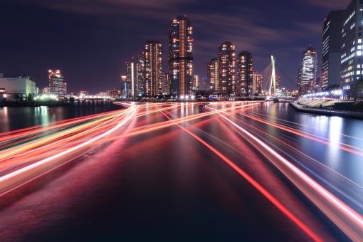 夜の隅田川を彩る屋形船の光跡の写真
