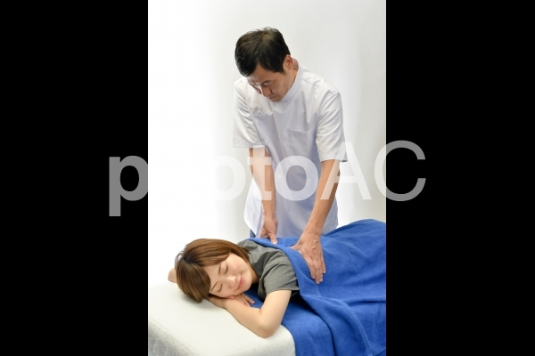 うつ伏せの女性患者に施術する整体師25の写真