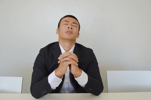 仕事がうまくいくように神に祈る新人君の写真